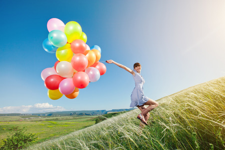 Happy woman with balloons running on green field. Holiday girl.