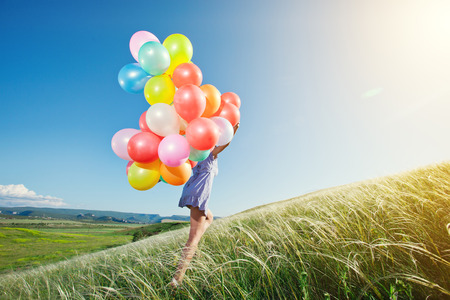 ballons: Happy woman with balloons running on the green field.