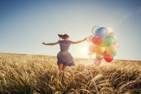 libertad: Muchacha que se ejecuta en el campo con los globos en la puesta del sol. Mujer feliz en la naturaleza. Foto de archivo