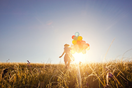 field and sky: Girl running on the field with balloons at sunset. Happy woman on nature.