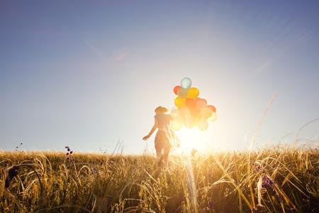 Meisje loopt op het veld met ballonnen bij zonsondergang. Happy vrouw op de natuur. Stockfoto