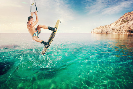 wakeboarding: Wakeboarder making tricks on the sea. Wakeboarding. Water sports on the beach. Stock Photo