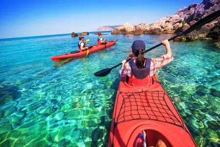 旅行: カヤック。海のカヤックに浮かぶ女性。海のレジャー活動。カヌーこぎ.