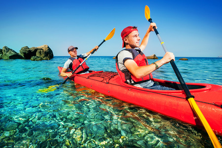 adventure sports: Two men paddle a kayak on the sea. Kayaking on island Stock Photo