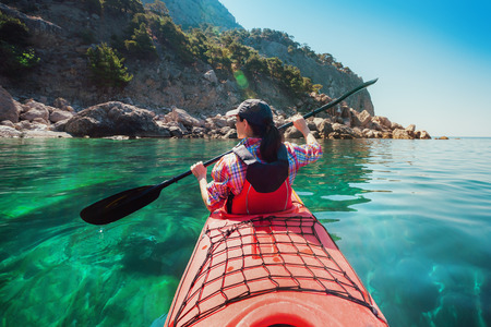 pull along: Woman kayaking at sea along the rocky shore of the island. Traveling by kayak.