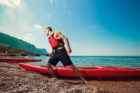 ocean kayak: Kayak. Hombre tira un kayak de la playa orilla. Actividades de ocio en el mar.