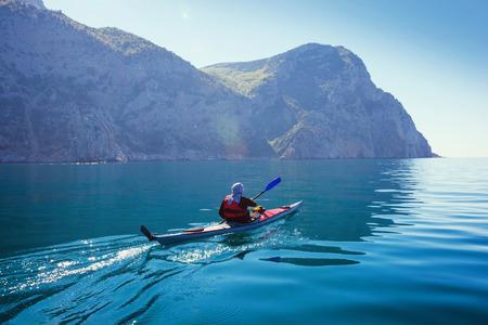 ocean kayak: Kayak. Gente kayak en el mar con agua azul en calma.