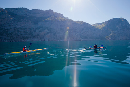 malawi: Kayak. People kayaking in the sea near the mountains. Activities on the water. Stock Photo
