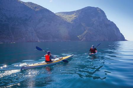 Kayak. Mensen kajakken in de zee in de buurt van de bergen. Activiteiten op het water. Stockfoto