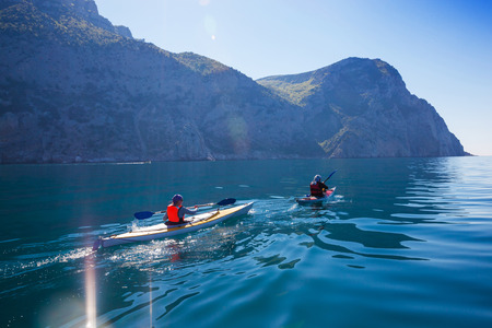 Kayak. People kayaking in the sea near the mountains. Activities on the water. Stock Photo