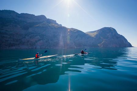 ocean kayak: Kayak. Gente kayak en el mar cerca de las monta�as. Actividades en el agua.
