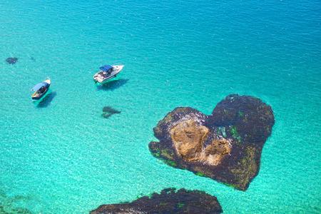Romantic island the shape of heart. Honeymoon travel by boat.