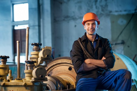 Portrait of a worker in the helmet near the turbine. Work the factory