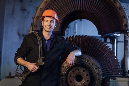 Portrait of a worker in the helmet near the turbine. Heavy industry.