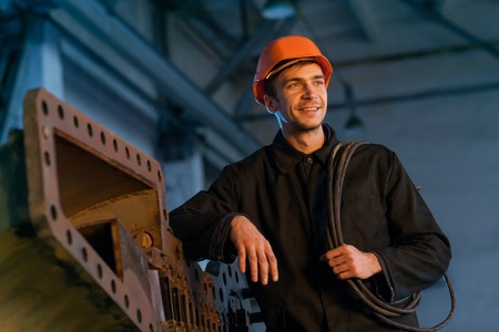 Worker in helmet near turbine with electric cable and wrench. Stock Photo