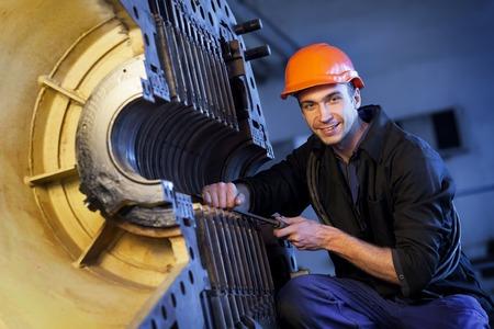 steam turbine: Portrait worker man in helmet near steam turbine. Heavy Industry Stock Photo
