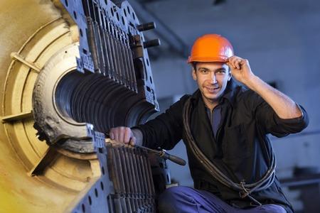 steam turbine: Portrait of a worker in the helmet near the steam turbine. Stock Photo