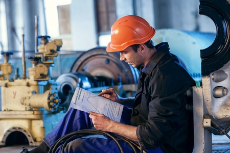 contruction: Worker on industry studying manual instructions for repair turbine.