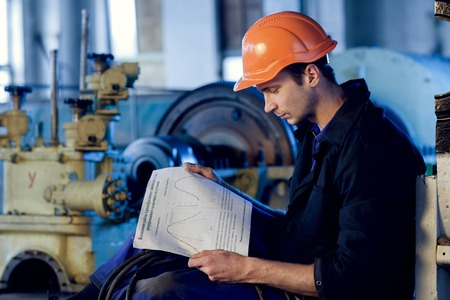 Worker on industry studying manual instructions for repair turbine.