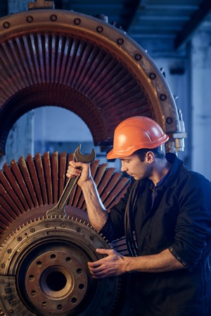 Portrait of a worker repairs powerful steam nuclear turbine. Stock Photo