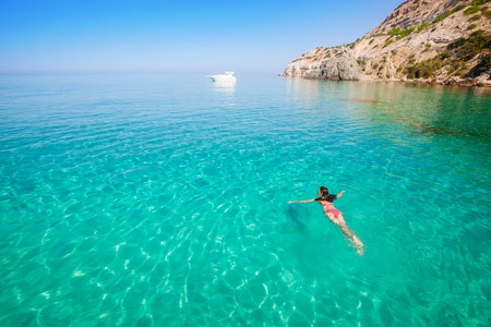 Beautiful woman bathing in clear sea. Active vacation on the beach.