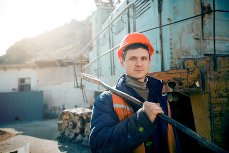 boilersuit: portrait young man in a helmet worker standing with a hammer on the shoulder