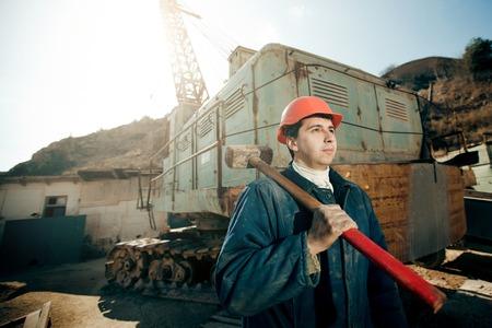 hombres trabajando: hombre trabajador retrato en casco con el martillo en el hombro Foto de archivo