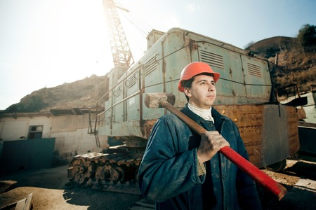 worker man: portrait worker man in helmet with hammer on the shoulder