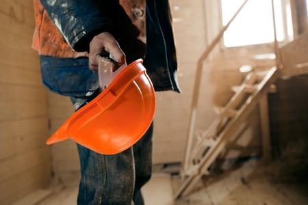 Worker holding a helmet in hands.
