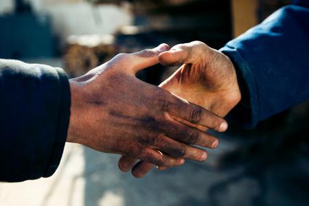 manos sucias: apretón de manos de dos trabajadores en una fábrica cerca