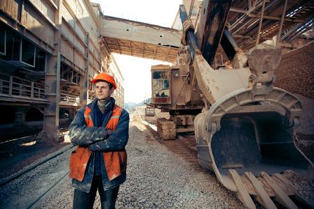 mineria: retrato del hombre que trabaja en un casco y ropa de trabajo cerca de la excavadora en una carrera Foto de archivo