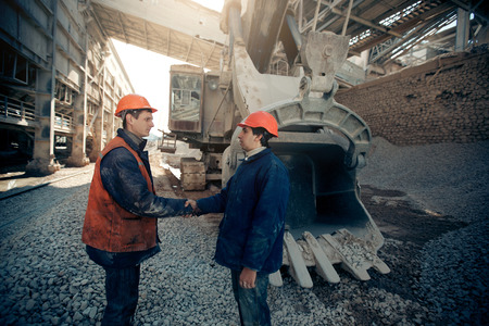 Workers shaking hands near the excavator mine industry.