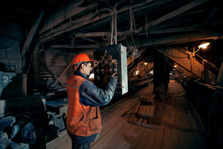 operating mines in the helmet presses a button on the remote control of the conveyor Reklamní fotografie - 42439234