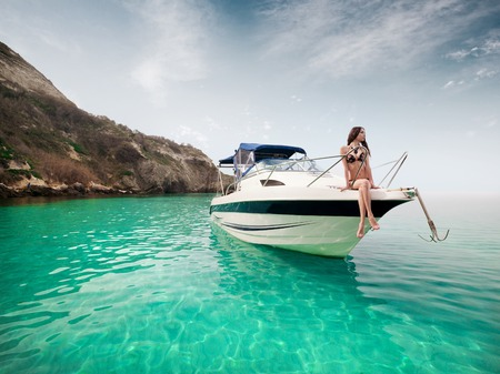 Beautiful young woman sitting on the boat a sunny summer day. Luxury vacation at sea. Stock Photo