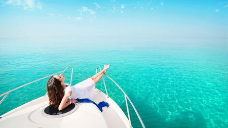 bow of boat: Woman lying on a private yacht in the sea. Stock Photo