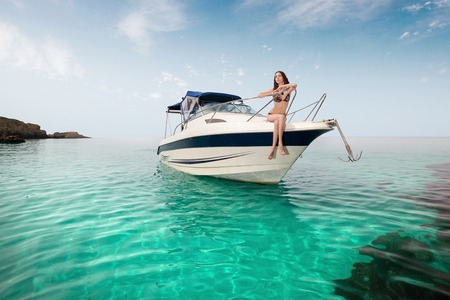 bow of boat: young beautiful girl sitting on a yacht at sea. Relaxing on the water