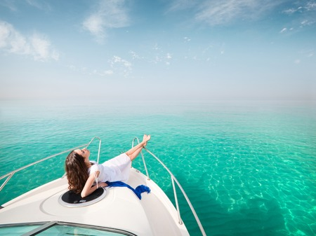 Young woman lies in white dress enjoying on yacht at the sea