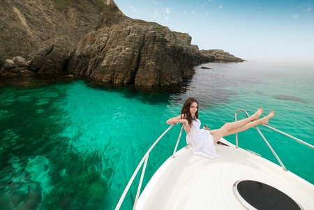Woman enjoying a yacht at sea on the islands with his feet up. Stock Photo