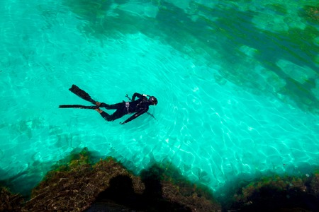 man in diving suit swims in the sea, top view. Activities on water