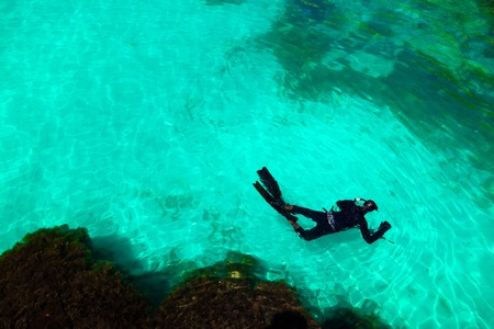 man in diving suit swims in sea, top view. Activities on water. diver