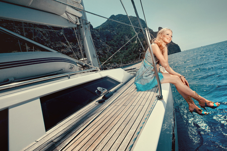 Happy woman on a luxury yacht in the sea. Beautiful girl on vacation