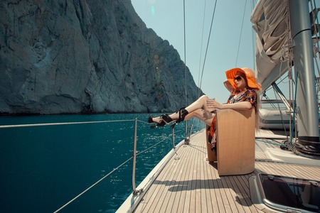 women legs: Happy beautiful woman on the luxury yacht sitting in the chair. Stock Photo