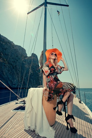 Happy beautiful woman on the luxury yacht sitting in the chair. 写真素材