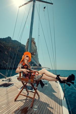Happy beautiful woman on the luxury yacht sitting in the chair. Stock Photo