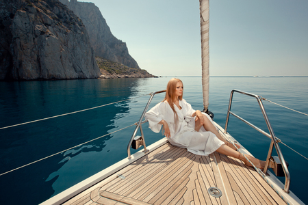 luxury lifestyle: sexy young woman sitting on the yacht in sunglasses and a in dressing gown
