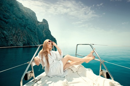 Young and pretty woman relaxing on luxury yacht floating in the sea.