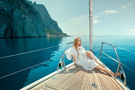 sexy young woman lies on yacht bow in sunglasses and dressing gown photo