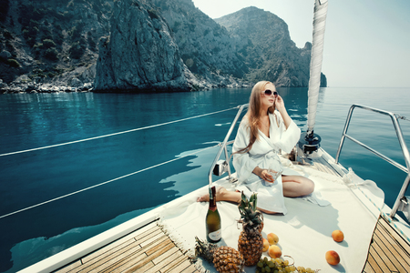 Luxury vacation at sea on yacht. Beautiful woman with wine, fruit and mobile phone on boat
