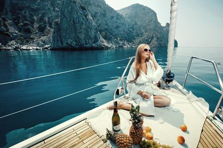 Luxusurlaub auf dem Meer auf Yacht. Schöne Frau mit Wein, Obst und Handy auf dem Boot