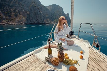 Vacances de Prestige en mer sur le yacht. Belle femme avec du vin, des fruits et téléphone mobile sur le bateau